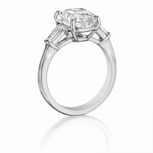 Henri Daussi engagement ring featuring a Signature Daussi Cushion cut accented by a tapered baguette on each side.  Set in 18kt white gold.